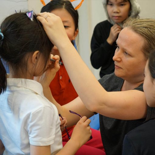 Female English drama teacher applying makeup on a Hong Kong student. Teacher and students preparing for a drama performance.