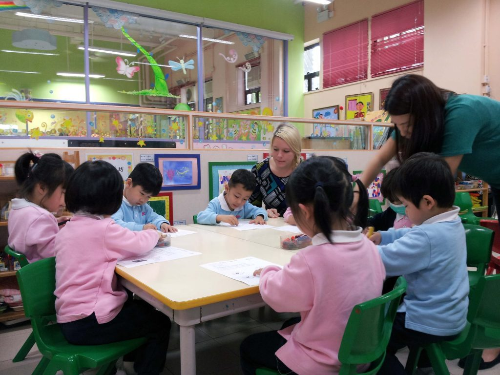 Female ESL teacher with kindergarten students doing worksheets.