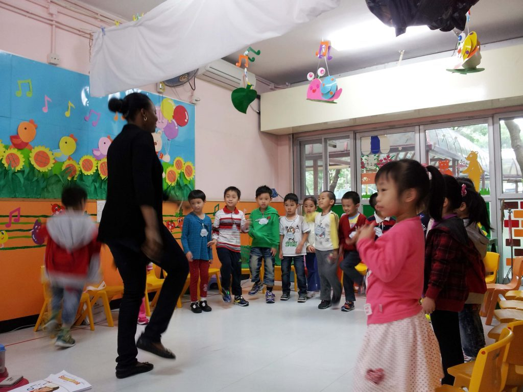 ESL teacher demonstrating dance movements in front of a group of kindergarten students